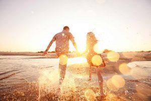 Happy couple running in ocean